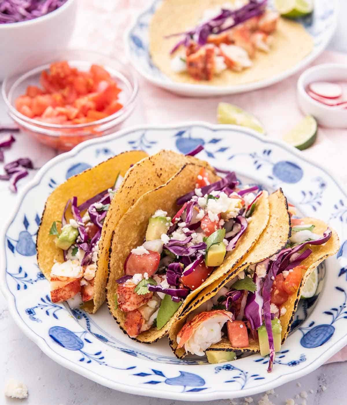 A blue and white plate holding three lobster tacos in a corn tortilla with ingredients in bowls in the background.