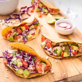 Pinterest graphic of a cutting board with four lobster tacos with small bowls of toppings on the board.