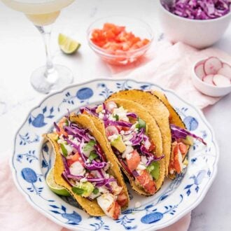 Pinterest graphic of a blue and white plate with three lobster tacos beside a cocktail drink and three bowls of chopped tomatoes, radishes, and cabbage.