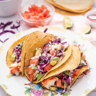Pinterest graphic of three lobster tacos on a plate with crumbled cheese around it along with a bowl of tomatoes, cabbage, and tortillas in the background.