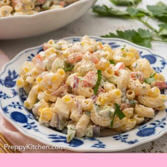 Pinterest graphic of a blue and white plate of macaroni salad in front of a serving bowl of the salad.