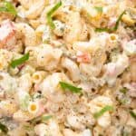 Close up of macaroni salad with parsley sprinkled on top.