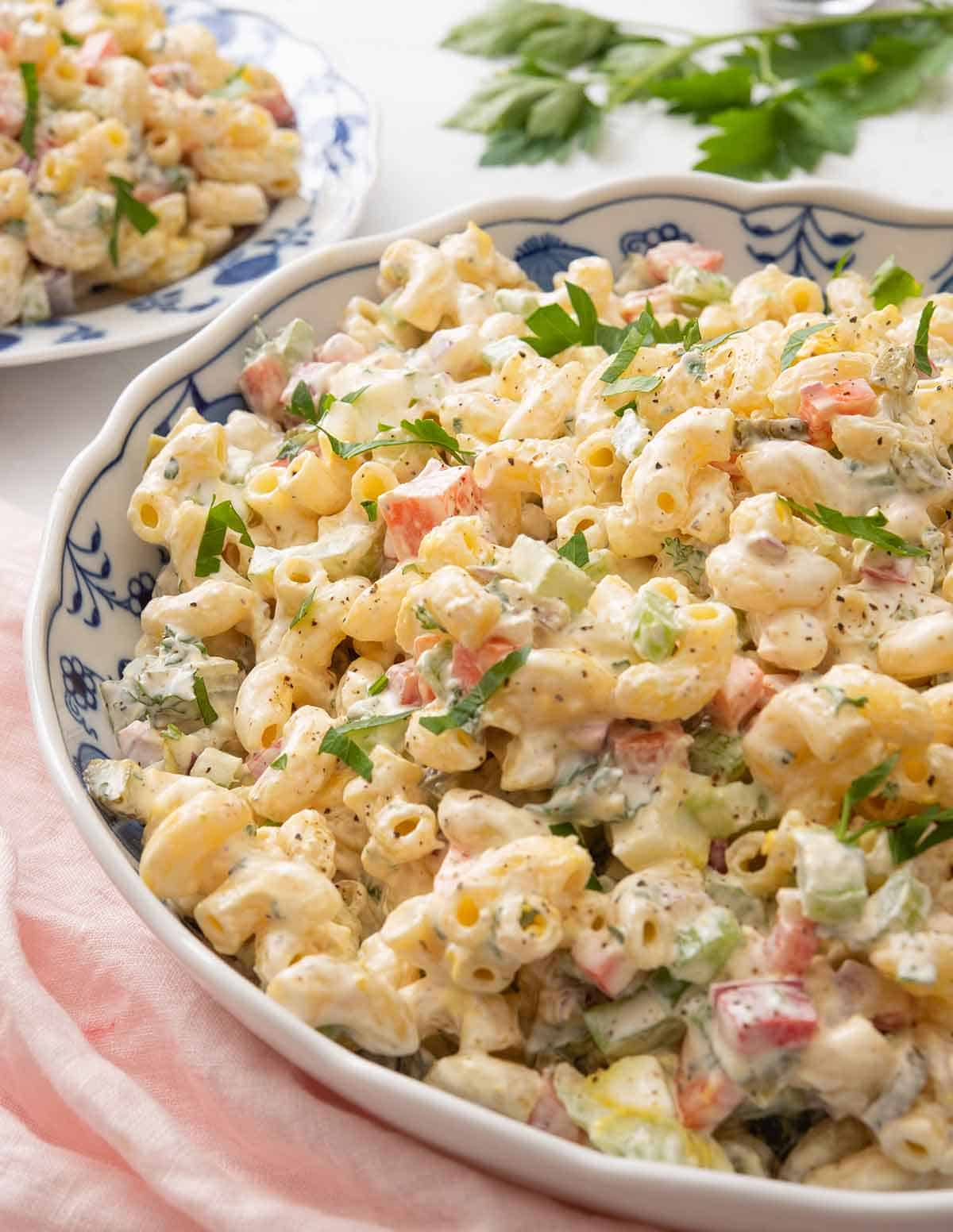 A large blue and white bowl of macaroni salad beside a pink linen.