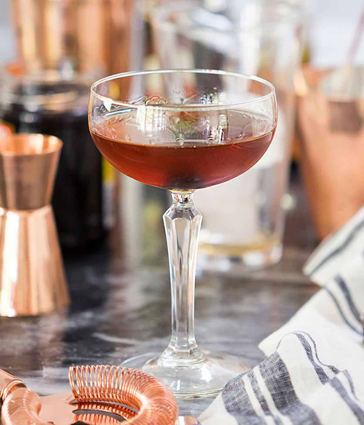 A Manhattan in a cocktail glass behind a linen napkin and strainer.