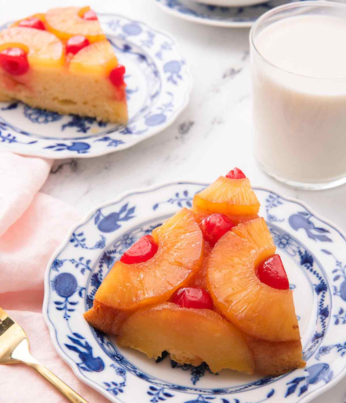 Two slices of pineapple upside down cake on blue and white plates with one in the foreground.