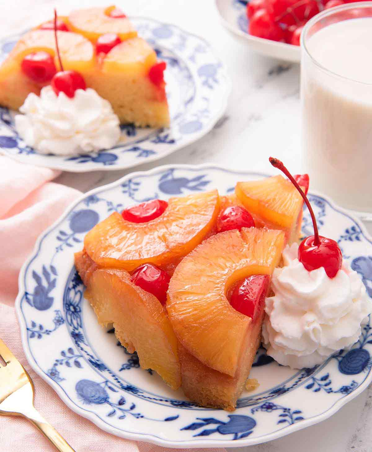 Two plates of pineapple upside down cake with one in the foreground, both with a dollop of whipped cream with a cherry on top.