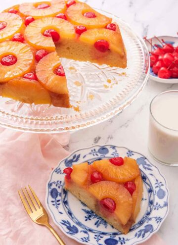 A pineapple upside down cake on a cake stand with a slice cut out and placed on a plate in front of it.