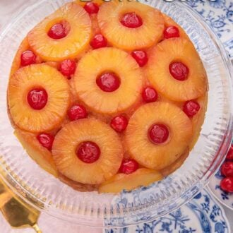 Pinterest graphic of an overhead view of a pineapple upside down cake on a clear cake stand.