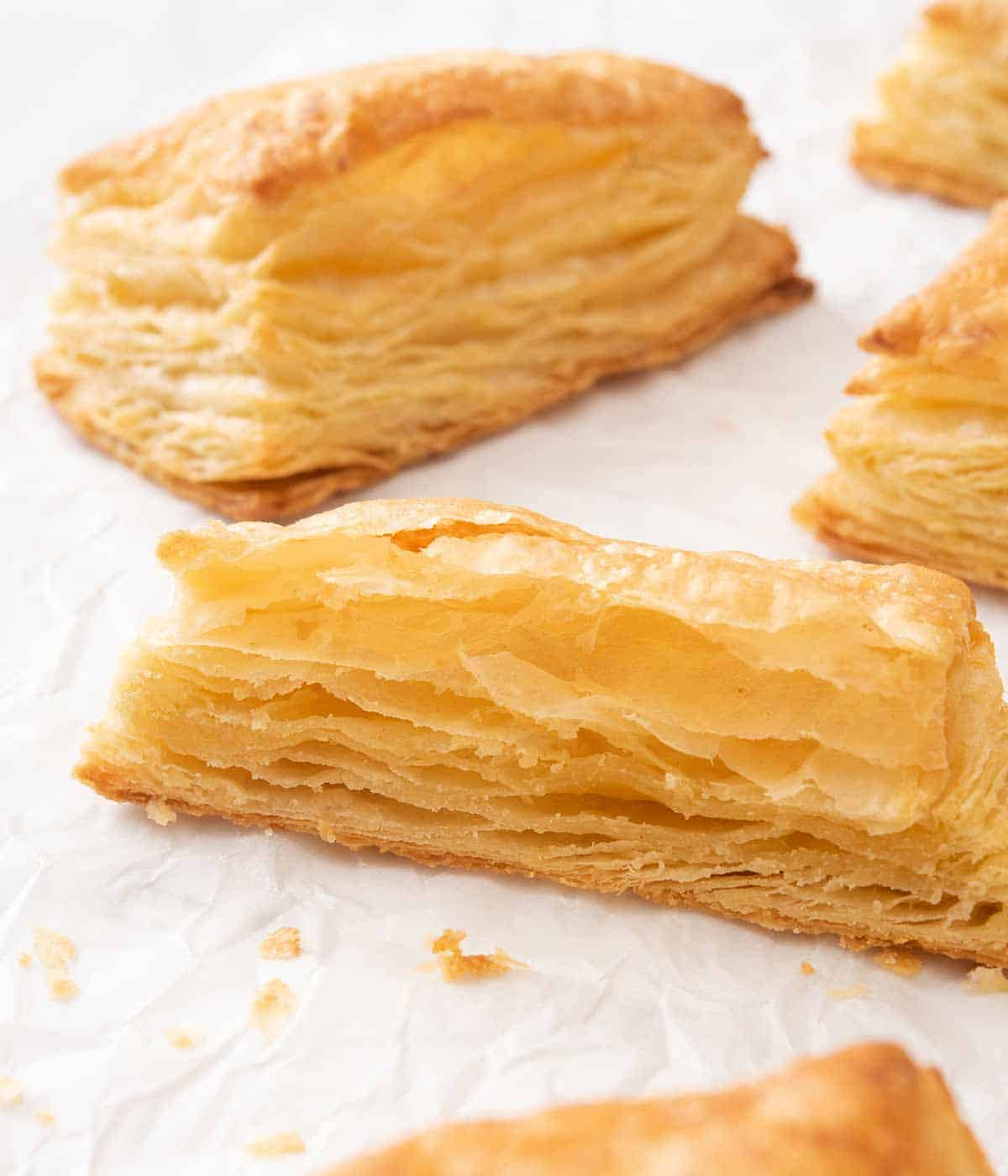 Puff pastry on a white surface with one cut in half, showing the flaky layers.