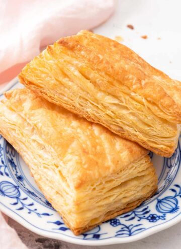 A blue and white plate with two puff pastries.