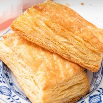 Pinterest graphic of two pieces of puff pastries on a white and blue plate.