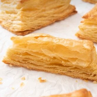Pinterest graphic of a few puff pastries with one cut in half, showing the layers.
