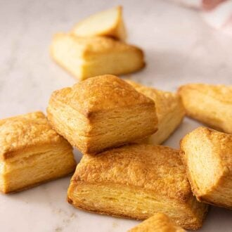 Pinterest graphic of a pile of puff pastries on a marble surface.