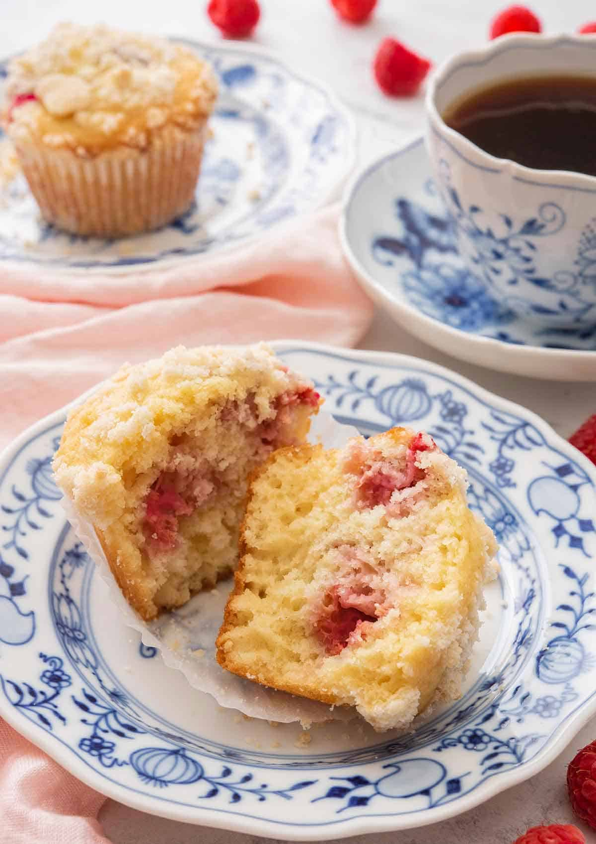 A raspberry muffin cut in half on a blue and white plate beside a cup of coffee and another muffin in the back.