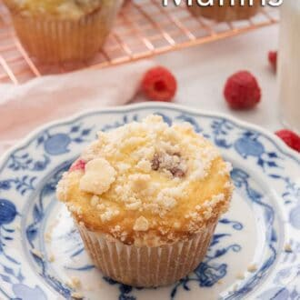 Pinterest image of a raspberry muffin with streusel on top. A cooling rack with more muffins are in the background.