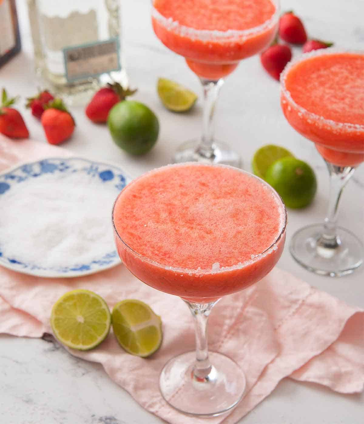 A set of three cocktail glasses with strawberry margarita beside a plate of salt, cut limes, and strawberries.