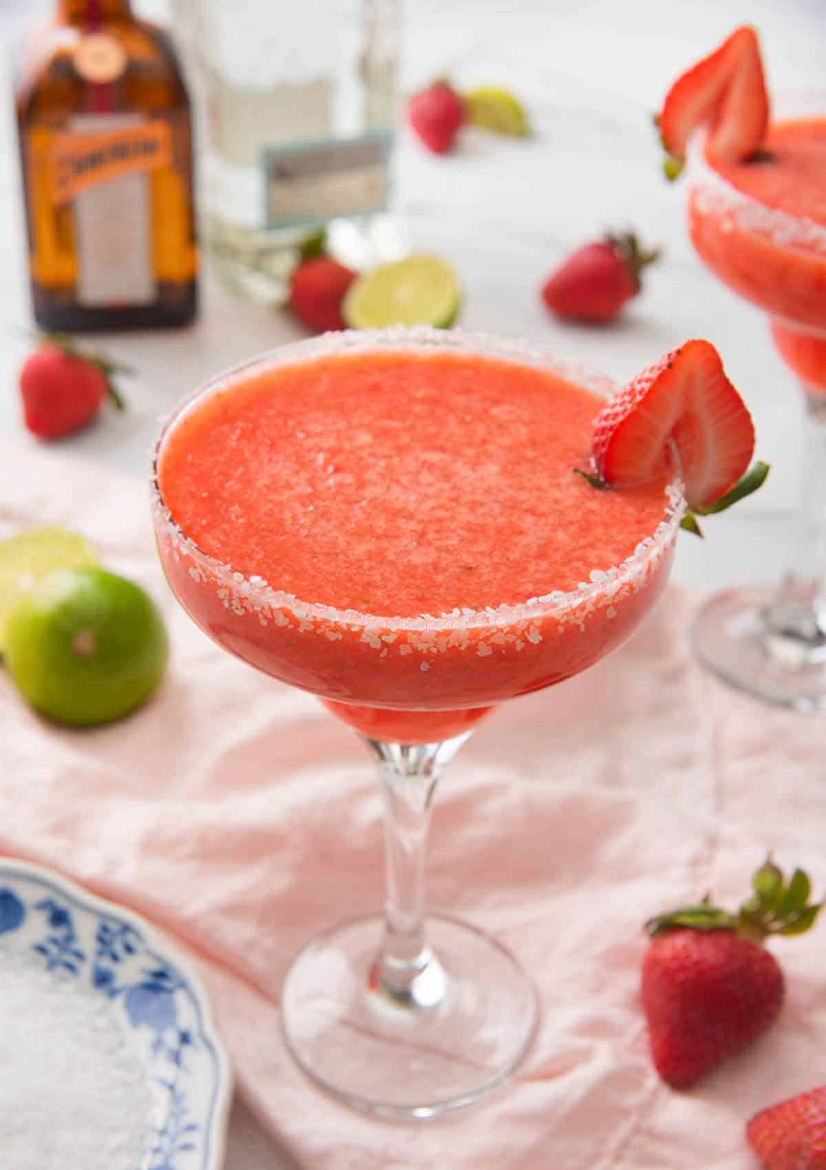 A strawberry margarita in a cocktail glass with a halved strawberry on the rim with the ingredients out of focus in the background.