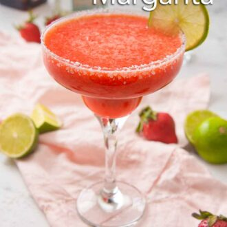 Pinterest graphic of a strawberry margarita in a cocktail glass with salt on the rim and a slice of lime as garnish on top of a pink linen napkin. Halved limes and strawberries are around it.