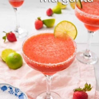 Pinterest graphic of three strawberry margaritas with a slice of lime as garnish with more strawberries and cut limes on the countertop.