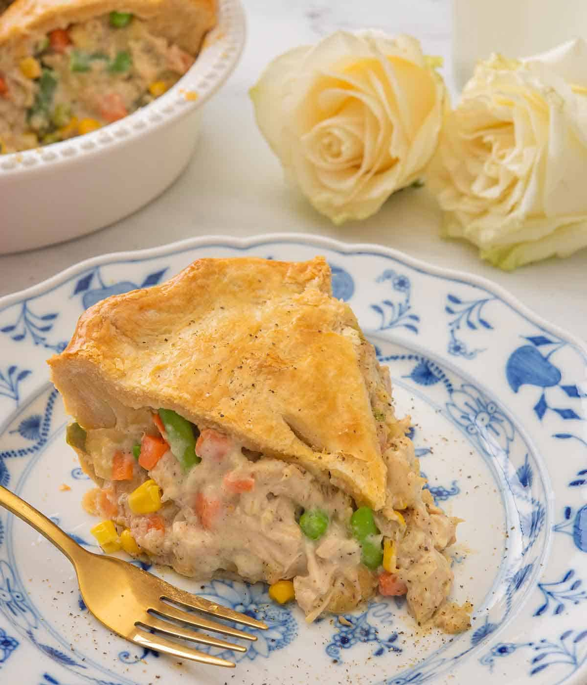 Close up of a slice of turkey pot pie on a white and blue plate with two white roses in the background.
