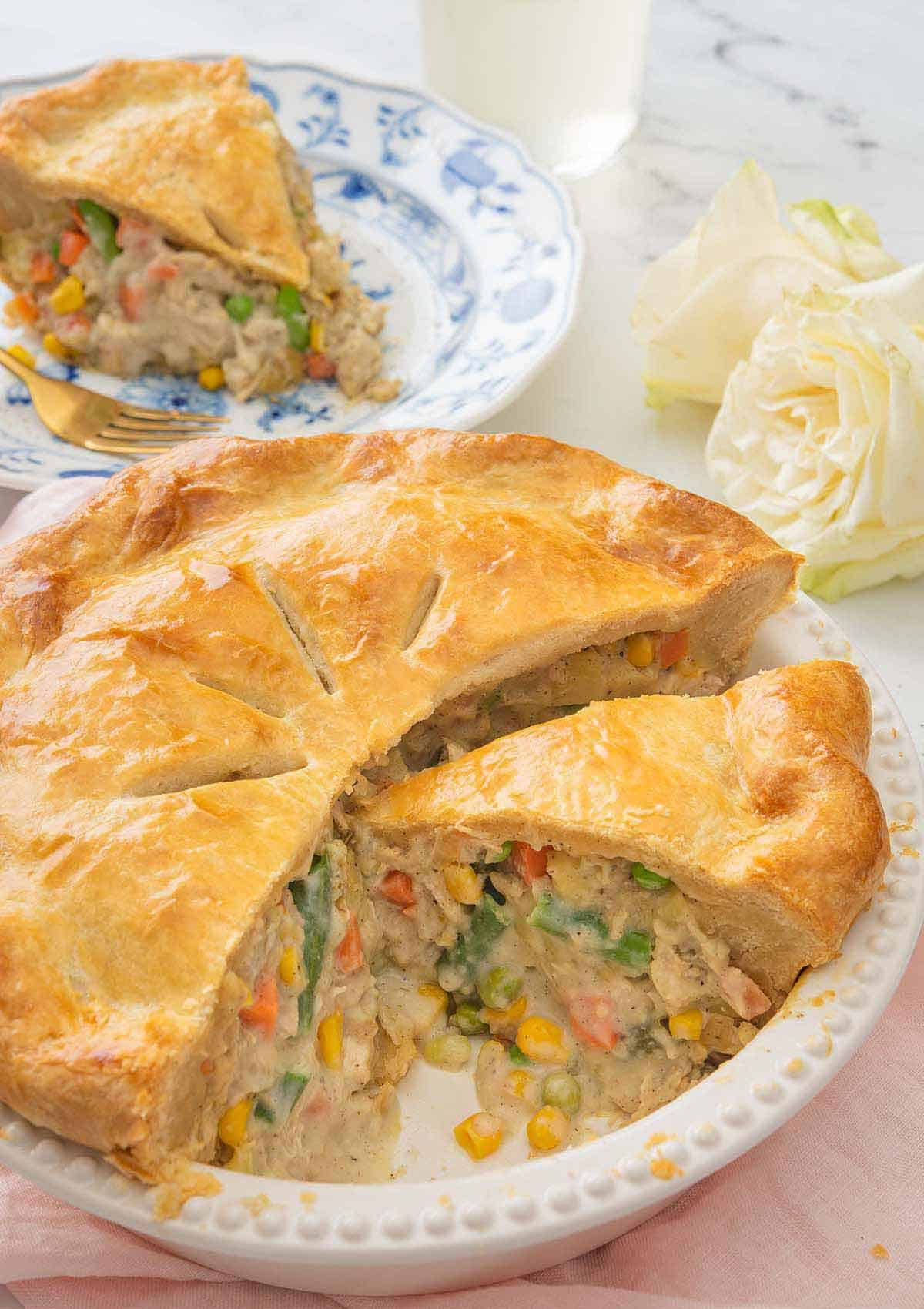 A turkey pot pie, cut opened with a slice removed and placed on a plate behind it.