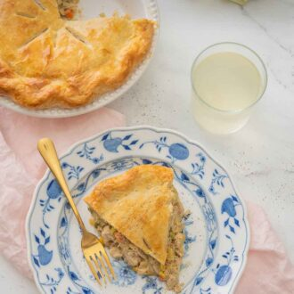 Pinterest graphic of a plate of turkey pot pie beside the cut pie over top of a pink linen napkin.