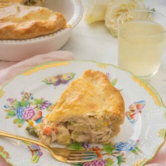 Pinterest graphic of a serving of turkey pot pie on a plate on top of a pink linen, beside a drink and the rest of the pie in the pie dish.