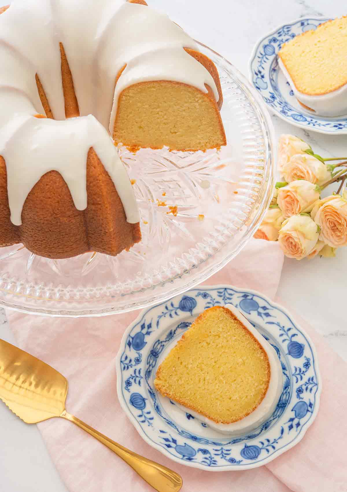 Overhead view of a vanilla Bundt cake with two slices cut out on their own small dessert plates.