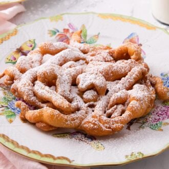 A funnel cake dusted with powdered sugar on a large plate.