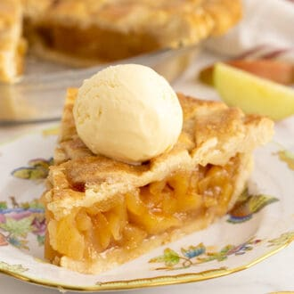 A piece of apple pie on a porcelain plate topped with a scoop of vanilla ice cream.