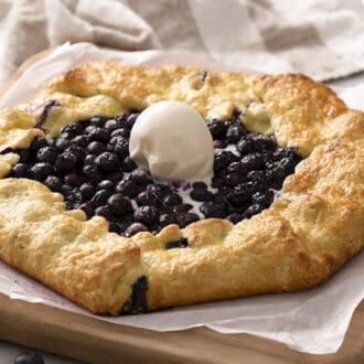 A blueberry galette topped with a scoop of vanilla ice cream on a cutting board.