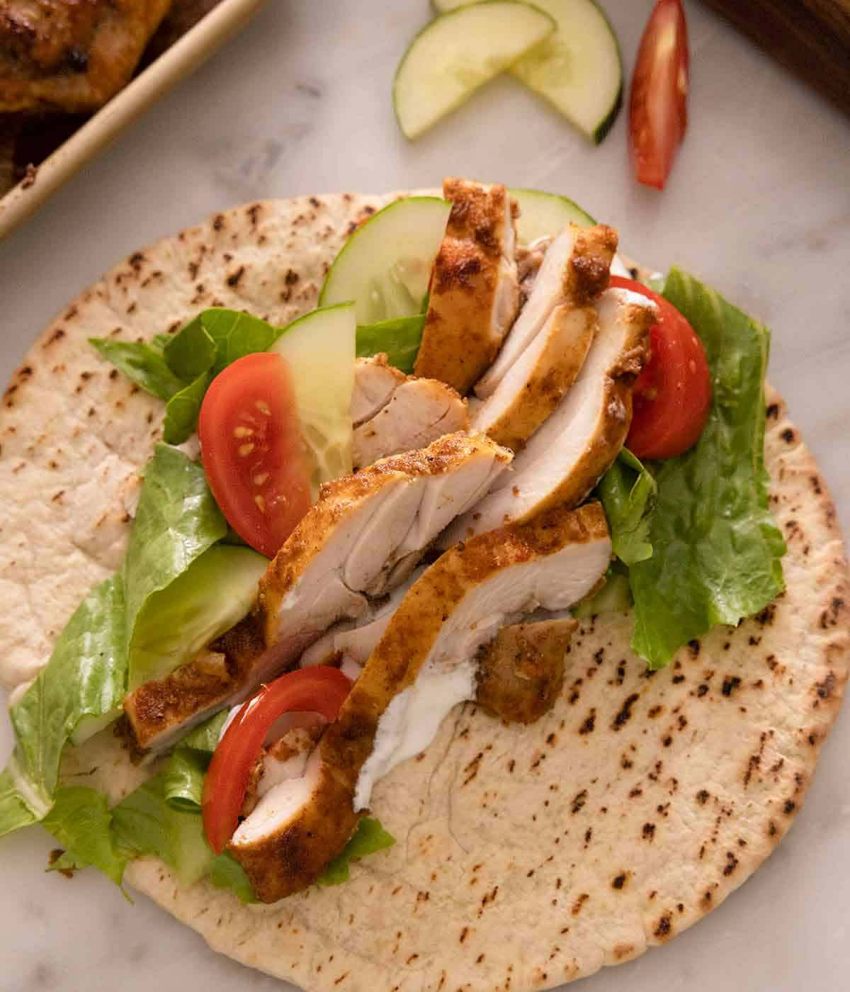 An opened pita with chicken shawarma with lettuce, tomatoes, and cucumbers.