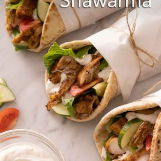 Pinterest graphic of three chicken shawarma with parchment paper wrapping them up.