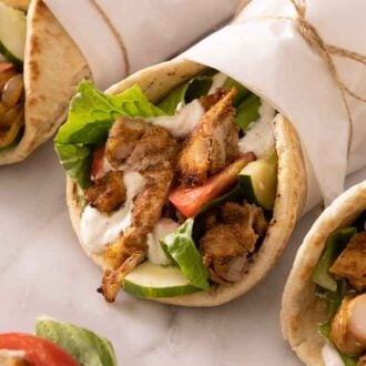 Three chicken shawarma with one in focus, all wrapped in parchment paper.