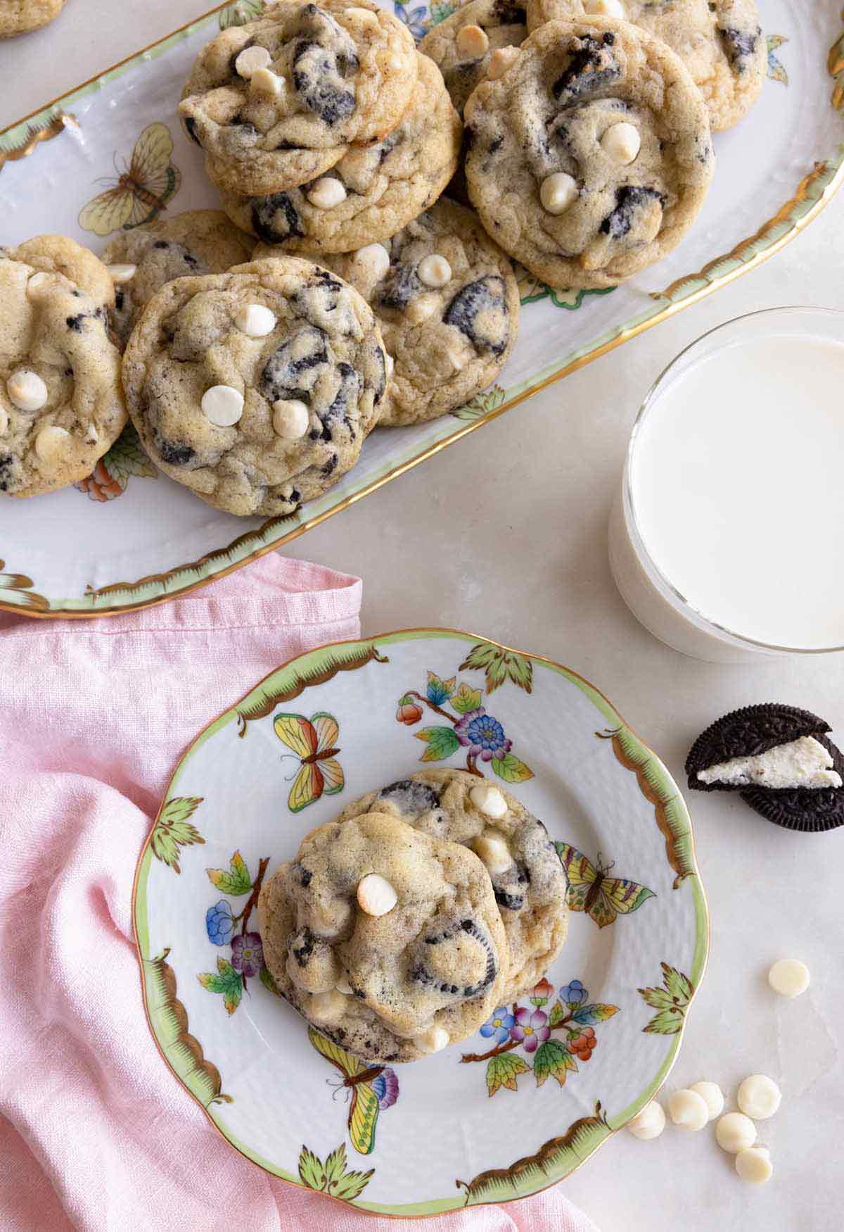 Overhead view of a serving platter of cookies and cream cookies with a small plate of them off to the side with a glass of milk.