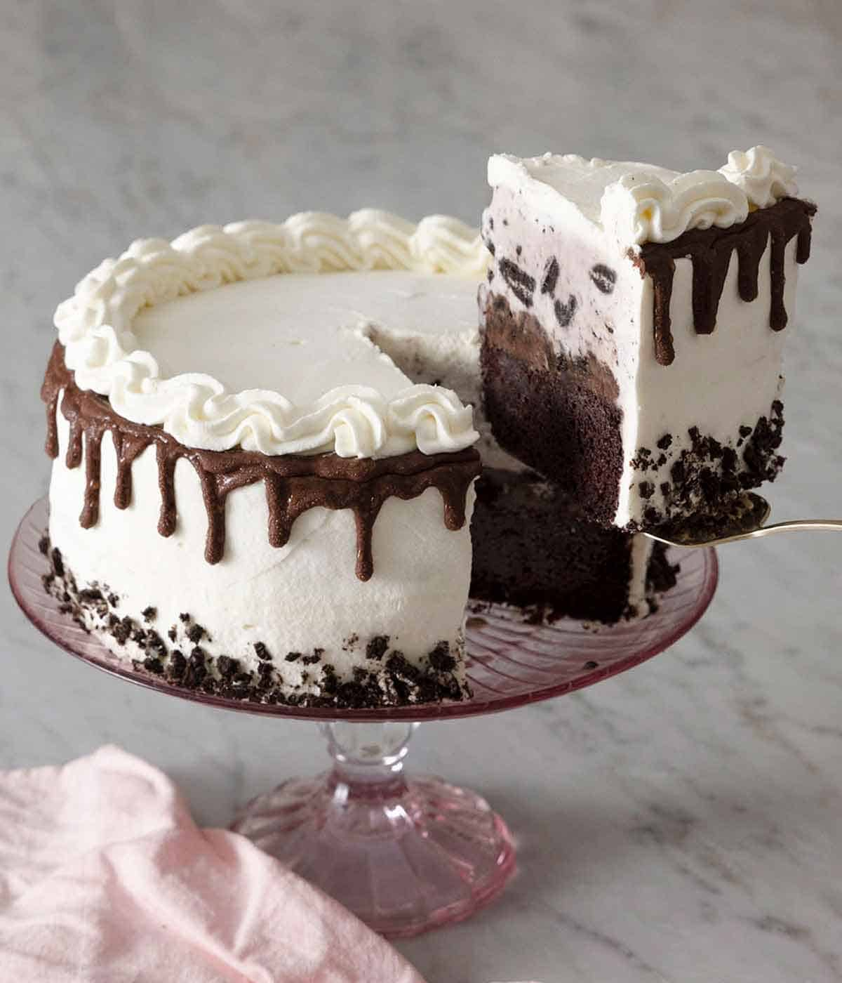 An ice cream cake on a cake stand with a slice being lifted up with a cake serving spatula.