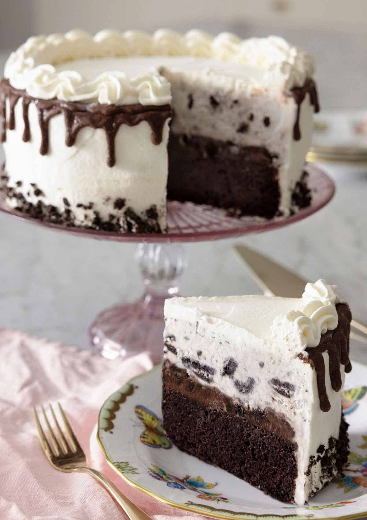 An ice cream cake on a cake stand with a slice cut out, on a plate in front.