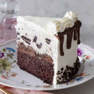 A slice of ice cream cake with Oreos on a floral plate.