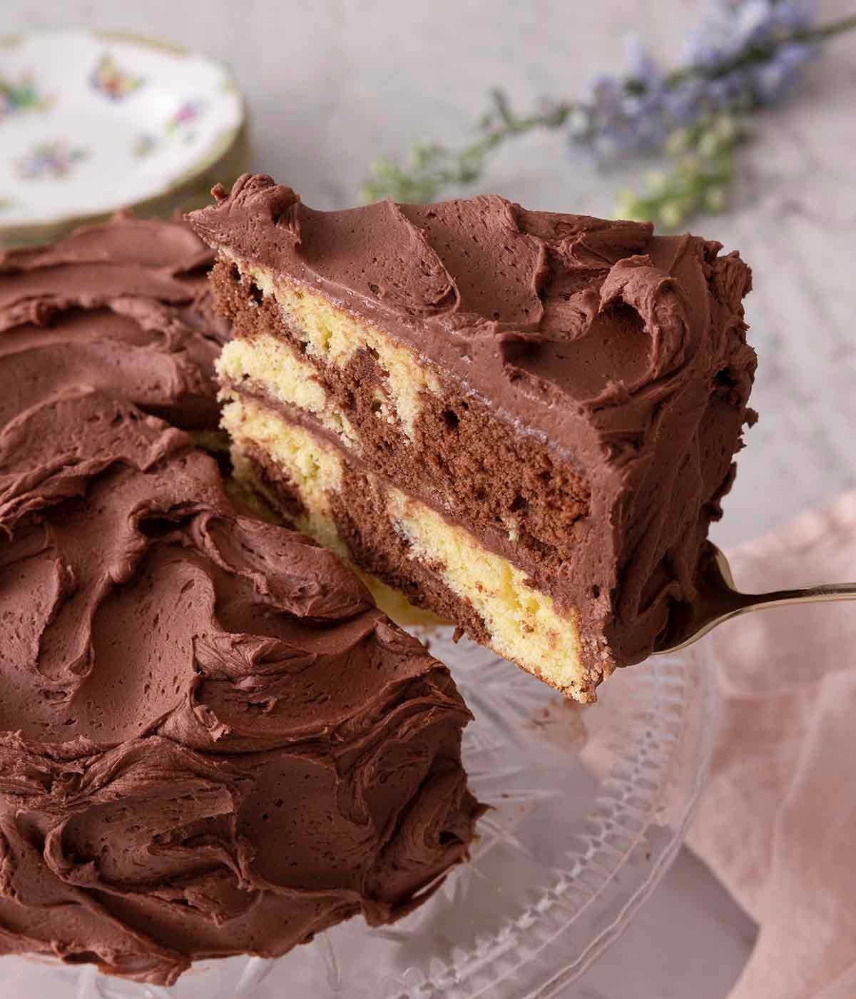 A slice of marble cake being lifted from the cake on a cake stand.
