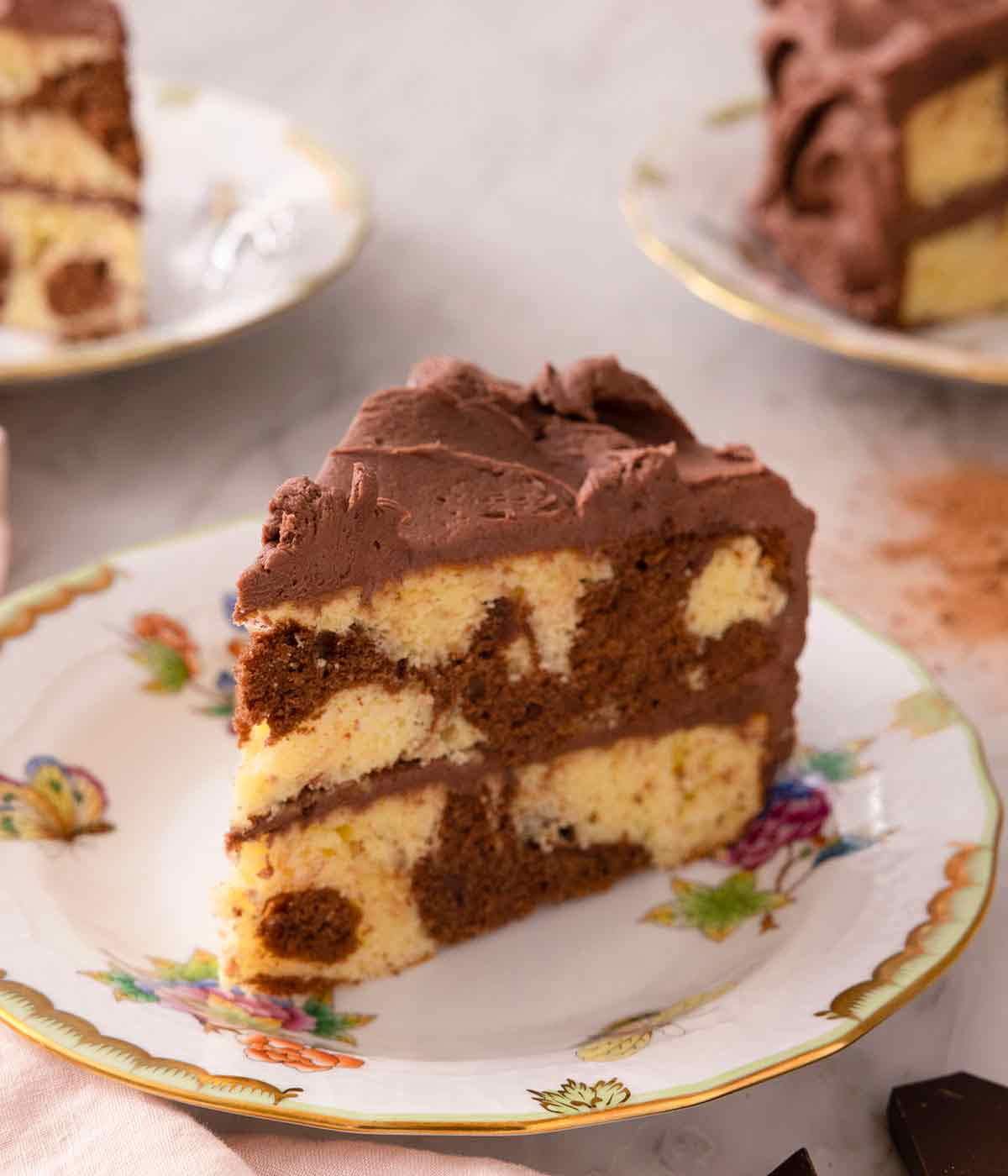 A slice of two tiered marble cake with chocolate buttercream frosting on a plate.