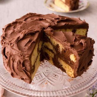 Pinterest graphic of a cake stand with a cut marble cake on top. One cut slice is on the stand still and the other on plates in the background.