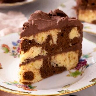 Close up of a slice of marble cake with chocolate frosting on a plate with a pink linen napkin and fork beside it.
