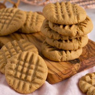 A group of peanut butter cookies stacked on a small wooden board.