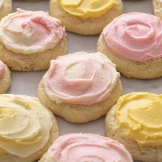 A group of sour cream cookies topped with pink and yellow buttercream on a marble surface.
