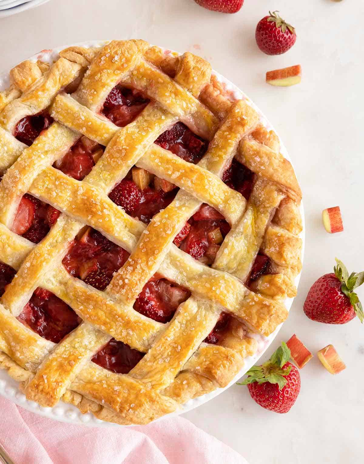 Overhead view of a strawberry rhubarb pie with a grid lattice.