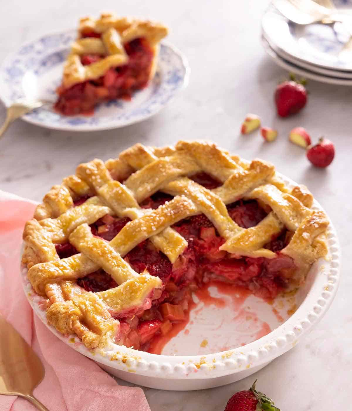 A white pie plate containing a strawberry rhubarb pie with a slice cut on, sitting on a plate in the background.
