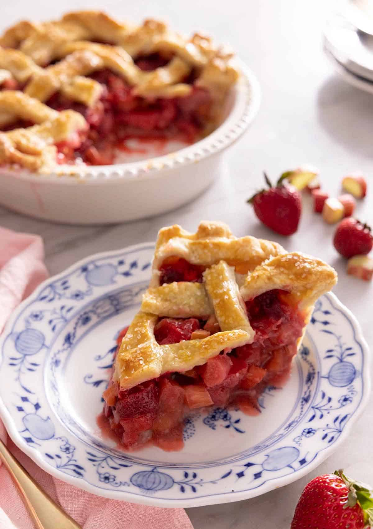 A slice of strawberry rhubarb pie on a plate with the rest of the pie in the ground out, out of focus.
