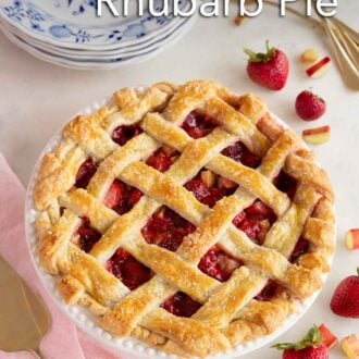 Pinterest graphic of a strawberry rhubarb pie with fresh strawberries and rhubarb scattered around it with a stack of plates and forks to the side.