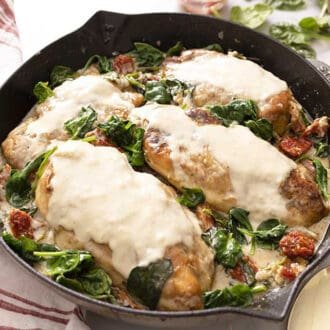An iron skillet with creamy tuscan chicken on a marble surface.
