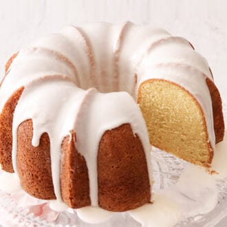A vanilla bundt cake with icing on a glass cake stand.